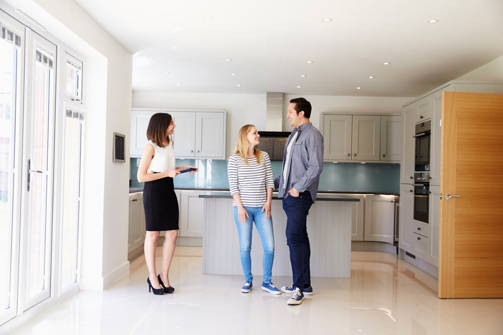 Realtor showing young couple around the property